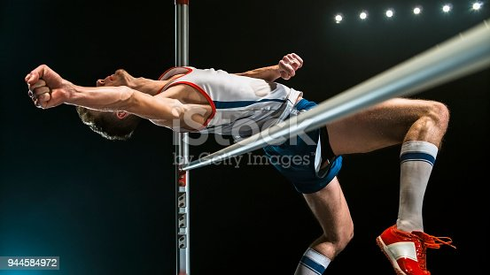 Male high jumper jumping over the bar against black background.
