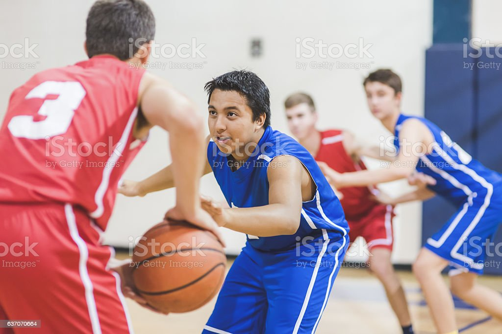 A teenage male basketball player is in the triple threat position...