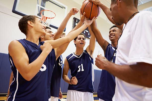 étudiants de lycée de l'équipe de basket de l'équipe ayant une conversation avec entraîneur - se regrouper photos et images de collection