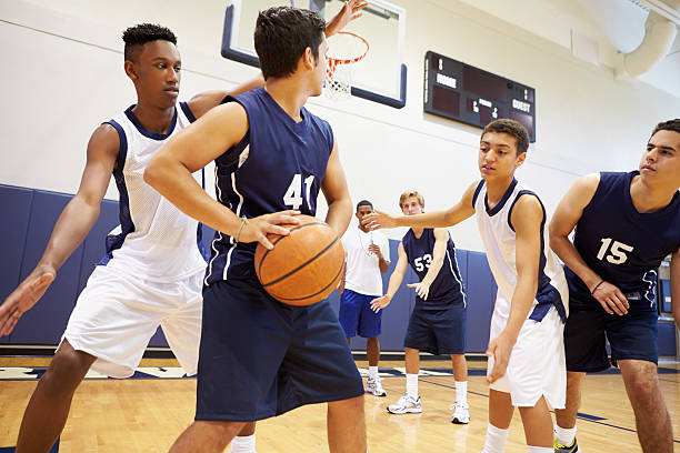 Male High School Basketball Team Playing Game Male High School Basketball Team Playing Game In Gymnasium basketball ball stock pictures, royalty-free photos & images