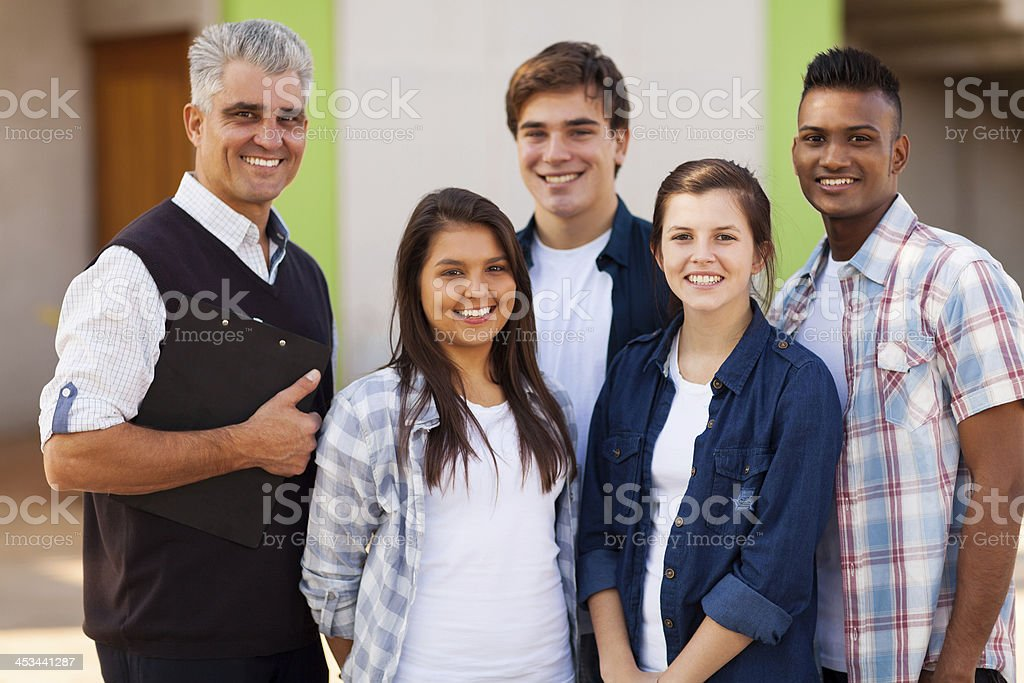 male high school teacher standing with students royalty-free stock photo