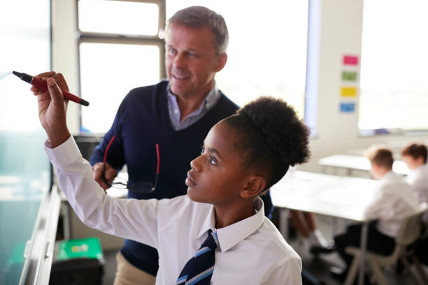 male high school teacher with female student wearing uniform using interactive whiteboard during lesson - private school stock photos and pictures