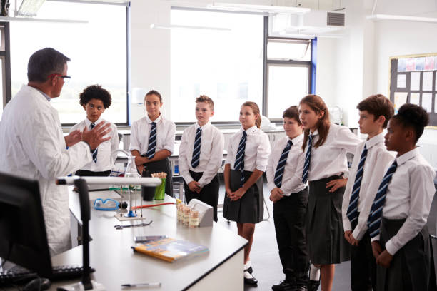 male high school tutor teaching high school students wearing uniforms in science class - private school stock photos and pictures