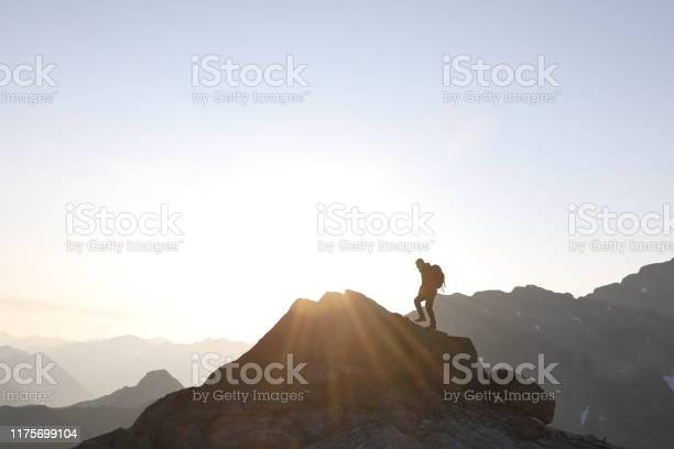 Photo of Male hiker ascends to mountain summit, sunrise