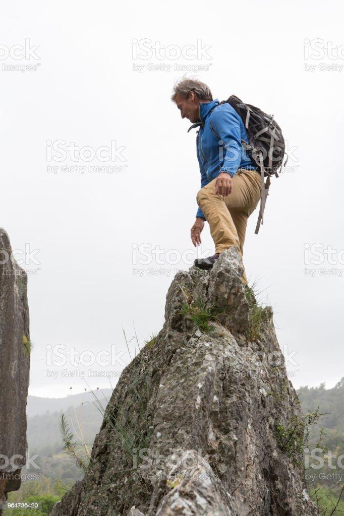 Male hiker climbing rock during rainstorm royalty-free stock photo