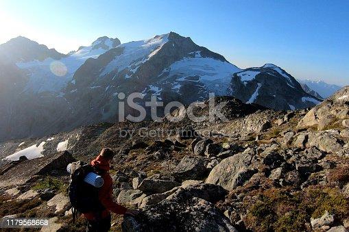 603993820 istock photo Male hiker crosses mountainside at sunrise 1179568668