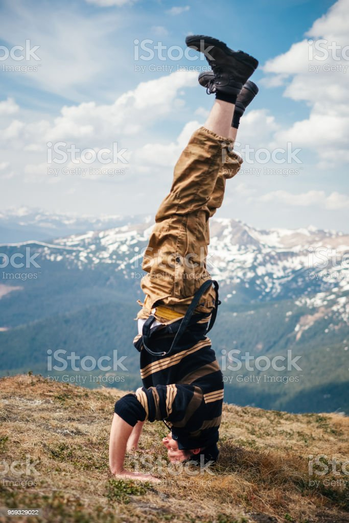 Male hiker headstand in mountains stock photo