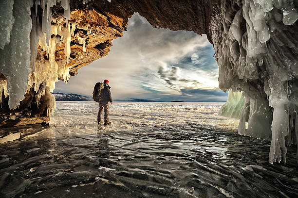 Male hiker in an ice cavern in winter stock photo