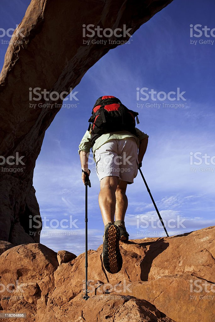 Male Hiker In Climb On Rocks Underneath Arch royalty-free stock photo