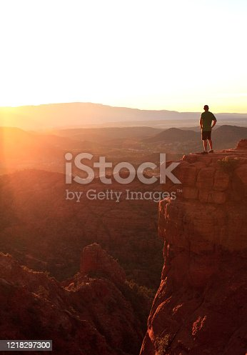 A male hiker - back view - in the beautiful red rocks of Sedona, Arizona. Image taken near Cathedral Mountain summit. Model is standing on a precarious lookout or viewpoint that is a popular location at sunset.
