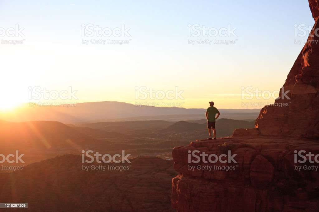 Male Hiker in Sedona at Dramatic Viewpoint at Sunset A male hiker - back view - in the beautiful red rocks of Sedona, Arizona. Image taken near Cathedral Mountain summit. Model is standing on a precarious lookout or viewpoint that is a popular location at sunset. 40-49 Years Stock Photo