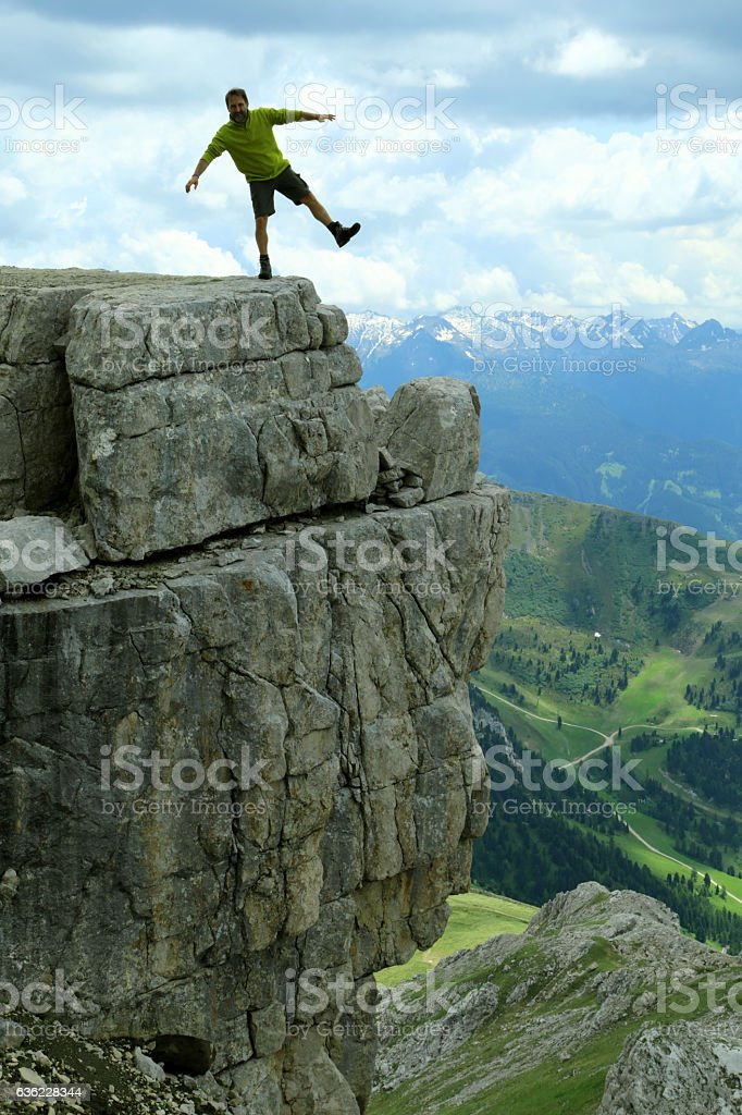 Male hiker is joking on the precipice edge, Latemar stock photo
