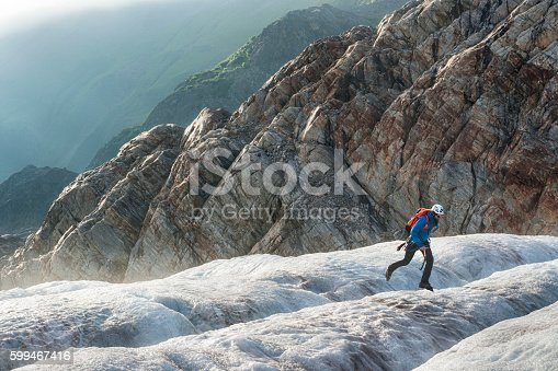 istock Male hiker jumps across an icy crevasse 599467416