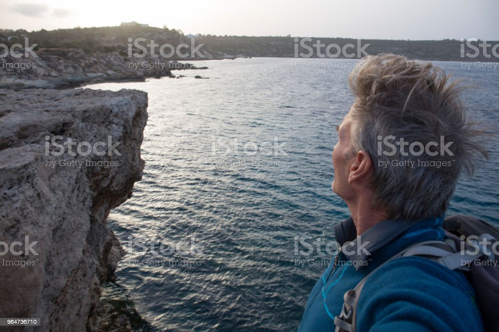 Male hiker looks out to sea, at sunrise royalty-free stock photo