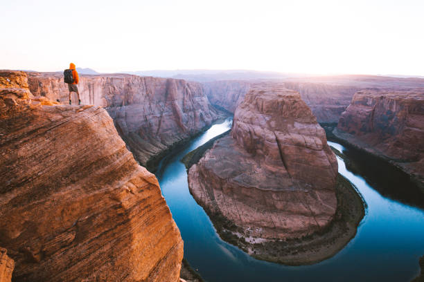 Male hiker overlooking Horseshoe Bend at sunset, Arizona, USA A male hiker is standing on steep cliffs enjoying the beautiful view of Colorado river flowing at famous Horseshoe Bend overlook in beautiful post sunset twilight on a summer evening, Arizona, USA lake powell stock pictures, royalty-free photos & images