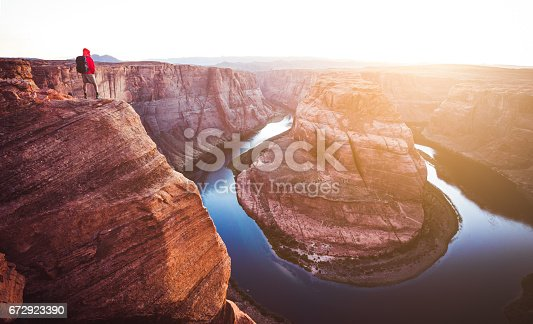 A male hiker is standing on steep cliffs enjoying the beautiful view of Colorado river flowing at famous Horseshoe Bend overlook in beautiful golden evening light at sunset in summer, Arizona, USA