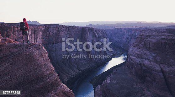 A male hiker is standing on steep cliffs enjoying the beautiful view of Colorado river flowing at famous Horseshoe Bend overlook in mystic post sunset twilight during blue hour in summer, Arizona, USA
