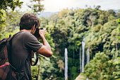 istock Male hiker photographing a waterfall in forest 580120812