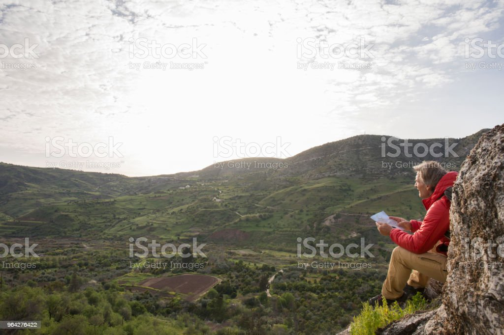 Male hiker relaxes on rock, in hills stock photo