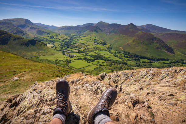Male hiker resting at summit of Cat Bells fell enjoying view of The Newlands Valley in the Lake District stock photo