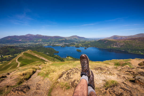 Male hiker resting at summit of Cat Bells looking at Lake Derwentwater and Keswick, England stock photo