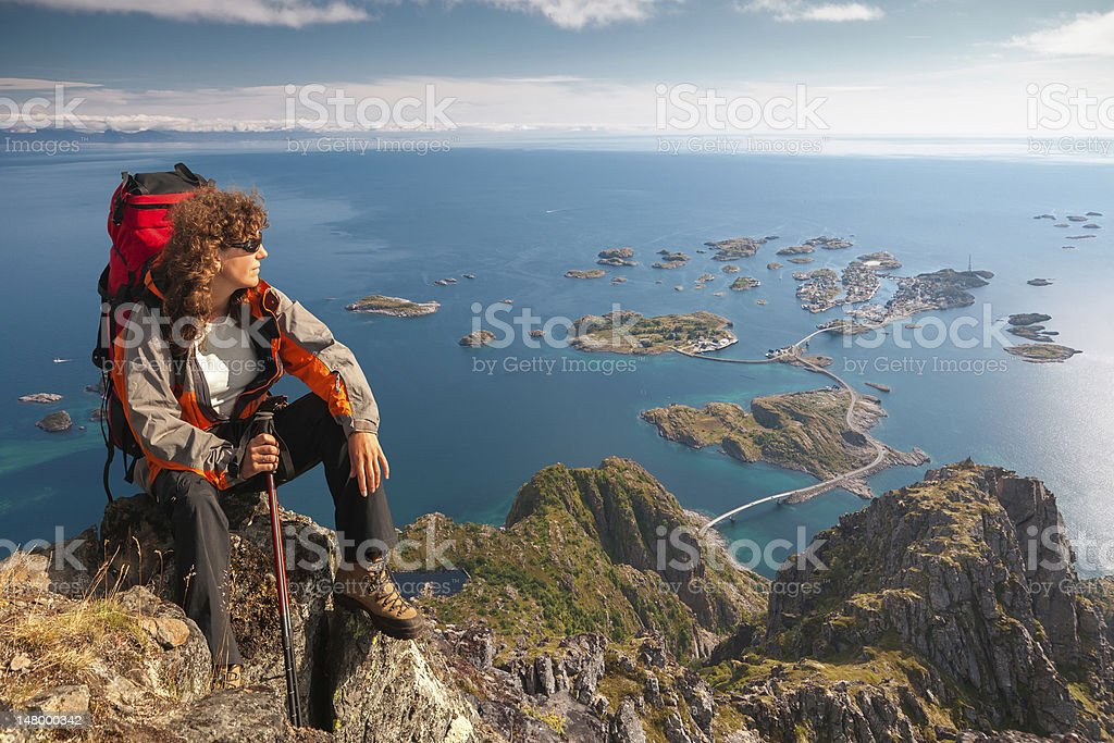 A male hiker seated atop a very high mountain in Lofoten stock photo