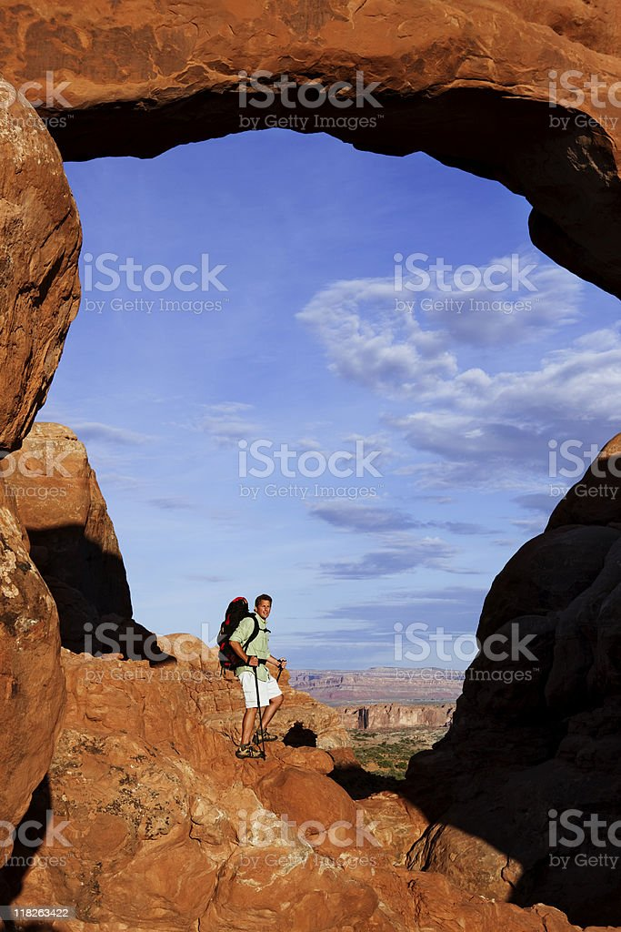 Male Hiker Standing On Rocky Ledge Under Huge Arch royalty-free stock photo