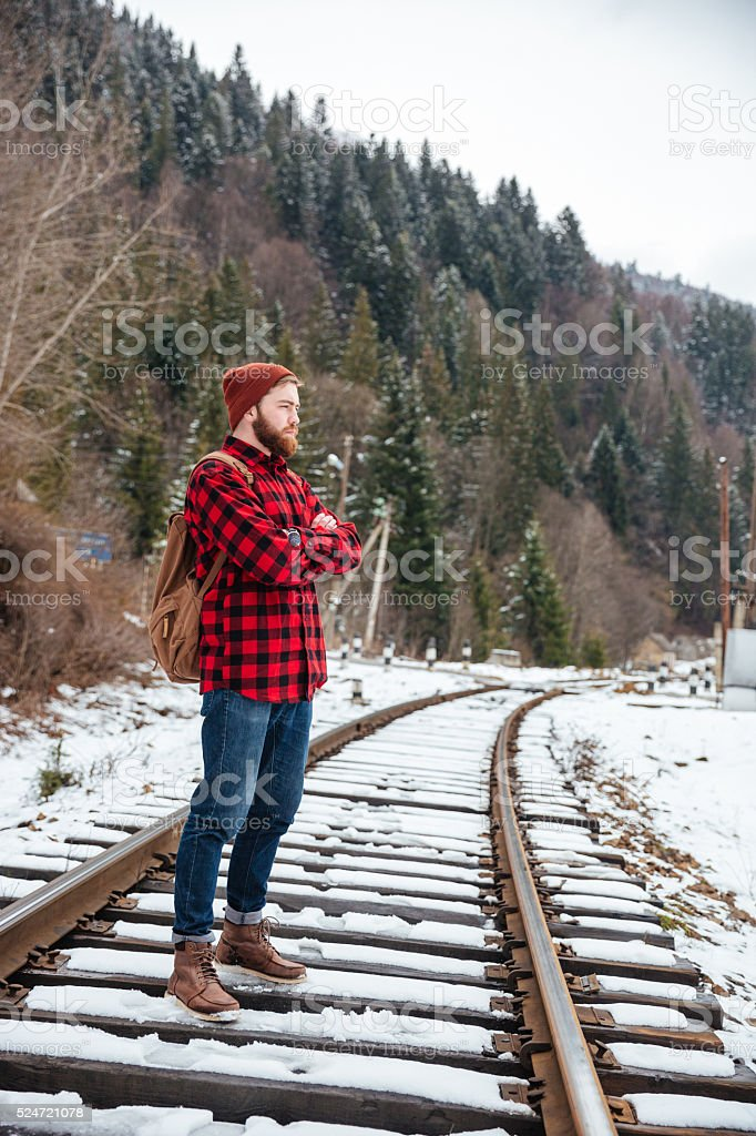 Male hiker standing with arms folded stock photo