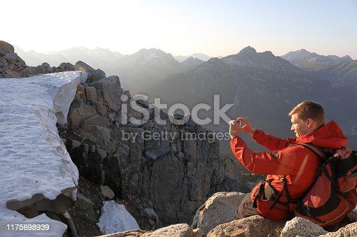 603993820 istock photo Male hiker takes pic on mountain ridge, sunrise 1175698939