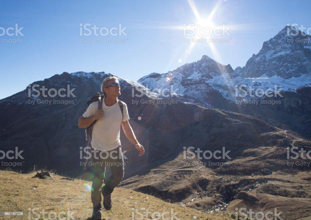 Male hiker treks through mountains in sunlight stock photo