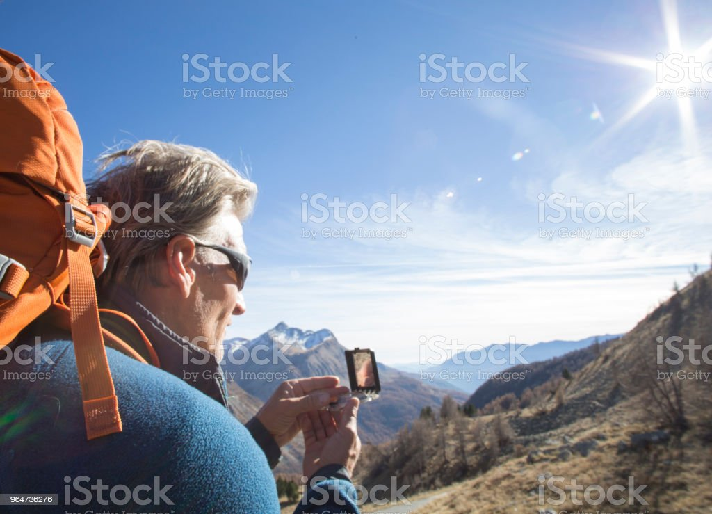 Male hiker uses compass in mountains royalty-free stock photo
