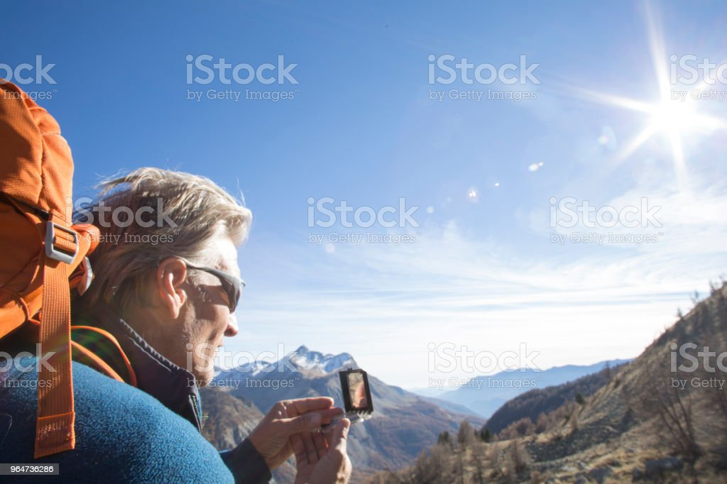 Male hiker uses compass in mountains stock photo