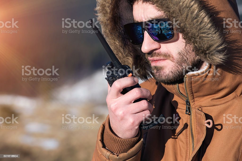 Male hiker using walkie talkie against mountain peaks stock photo