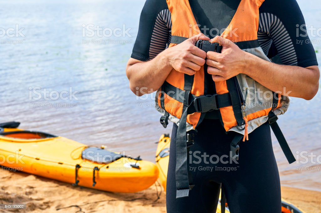 Male hiker wearing wetsuit putting on a life vest stock photo