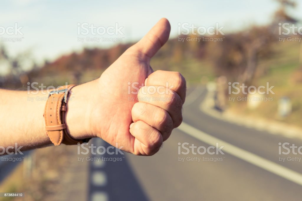 Male hitchhiker holding thumbup on the side of the road stock photo