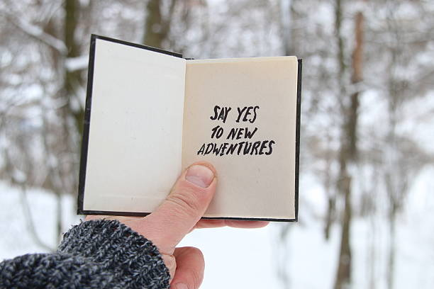 male holding a book with the inscription say yes to - neue abenteuer stock-fotos und bilder