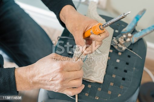 Male holding soldering iron tool repairing, electrical wire connection, soldering with a soldering iron.