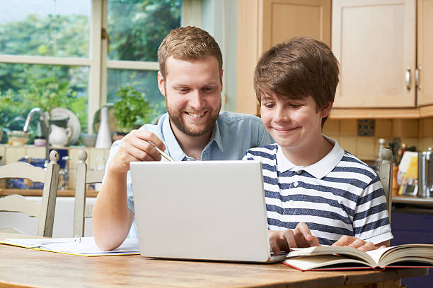 Male Home Tutor Helping Teenage Boy With Studies stock photo