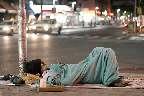 male homeless sleeping in a street - homelessness stock photos and pictures