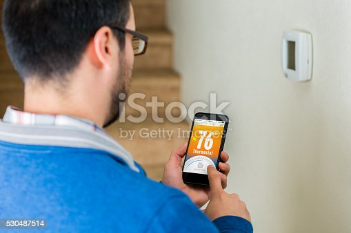 istock Male homowner uses smart phone to control thermostat 530487514