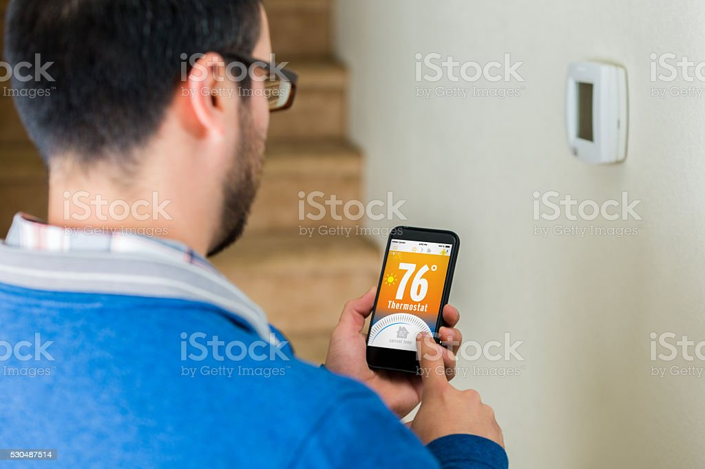 Male homowner uses smart phone to control thermostat stock photo