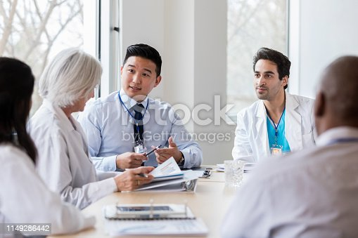 Mid adult male hospital administrator gestures while discussing hospital business with a female doctor during a staff meeting.