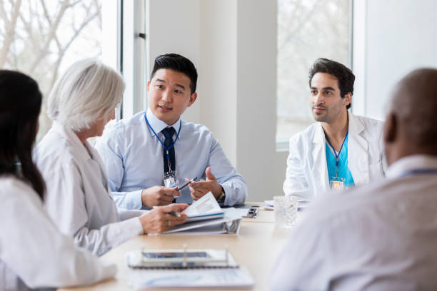 male hospital administrator talks with female doctor - cheap stock pictures, royalty-free photos & images