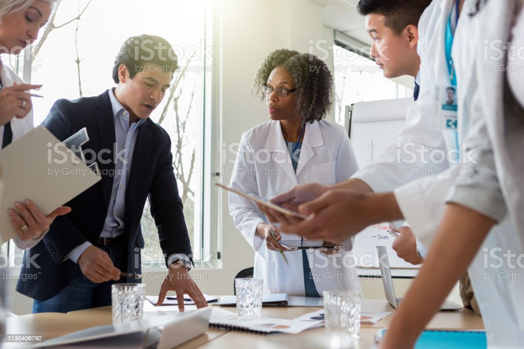 Attentive healthcare professionals meet with a mid adult male...
