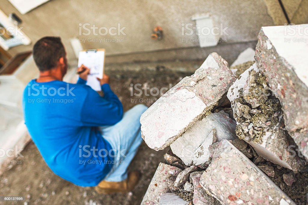 Male housing inspector taking notes on problem area of home stock photo
