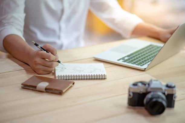 mannelijke illustrator handtekening wereldkaart schets op notebook papier werken met laptop computer en film camera op houten tafel. grafisch ontwerper maken van illustraties voor online reizen inhoud. - schepping stockfoto's en -beelden