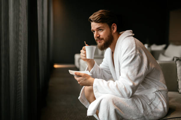 male in bathrobe relaxing while drinking tea - accappatoio foto e immagini stock