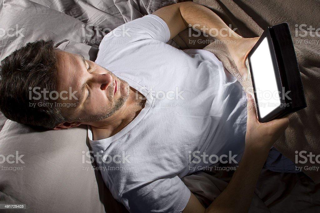 Hombre en la cama de navegar por la Internet con un comprimido - Foto de stock de Insomnio libre de derechos