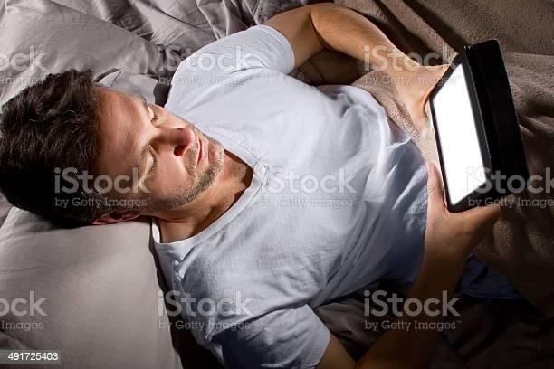 Hombre En La Cama De Navegar Por La Internet Con Un Comprimido Foto de stock y más banco de imágenes de Insomnio