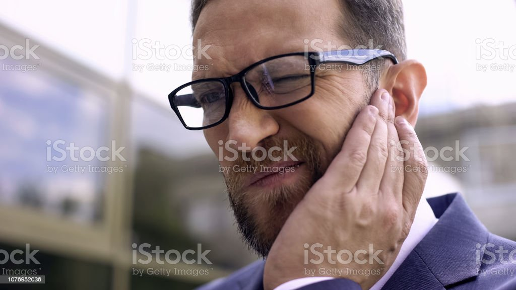 Male in eyeglasses has ear pain, bacterial infection, inflammation,...